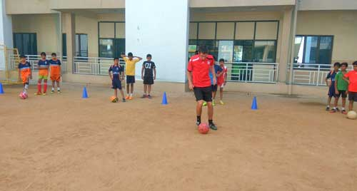 International Coach training football to JHS Kids